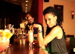 Junge Frau in einer Bar trinkt einen Cocktail