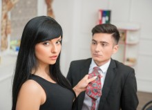 Businesswoman flirting and pulling her colleague by the tie, rel