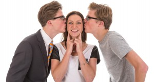 Male twins kissing a beautiful woman
